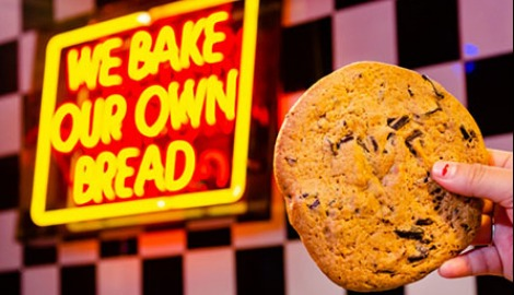 "A chocolate chip cookie held up in front of a sign that reads, ""We Bake Our Own Bread"""